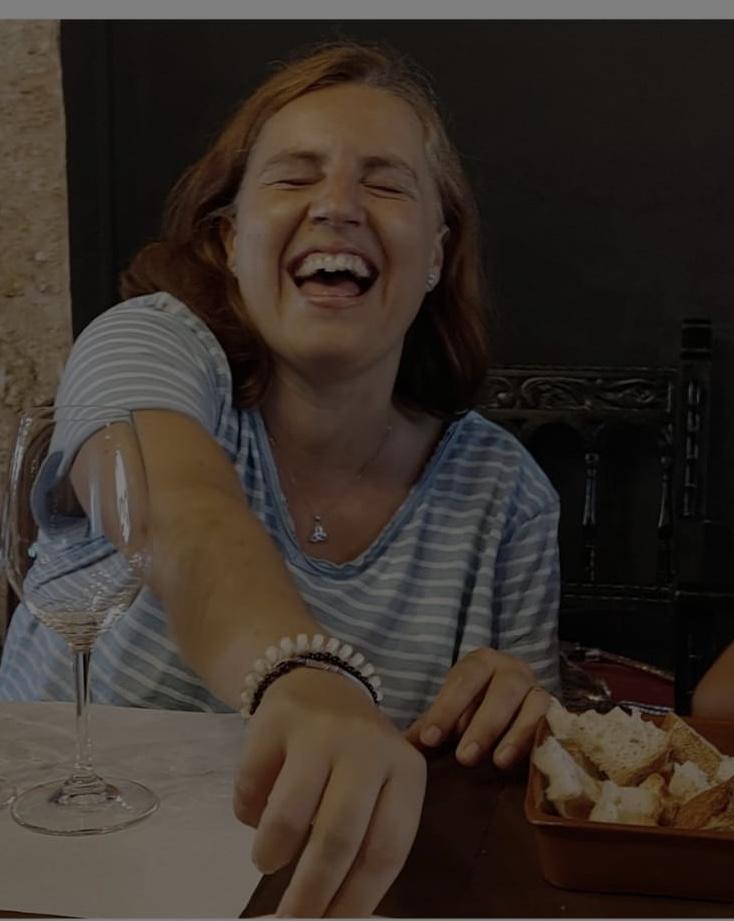 Nuria, con una sonrisa, degustando pan con aceite