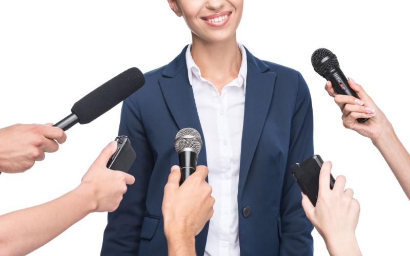 una mujer siendo entrevistada por diferentes personas